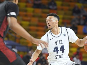 Utah State guard Marco Anthony (44) dribbles the ball as San Diego State forward Keshad Johnson (0) defends during the second half of an NCAA college basketball game Saturday, Jan. 16, 2021, in Logan, Utah. (Eli Lucero/The Herald Journal via AP, Pool)