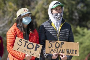 (Rick Egan   The Salt Lake Tribune) Chi Cheyenne Liang and Boone Hogg hold signs as they listen to a speaker, during a National Day of Protest to stop anti-Asian violence at a rally at the International Peace Gardens at Jordan Park, on Saturday, March 27, 2021.Cheyenne Liang Boone Hogg