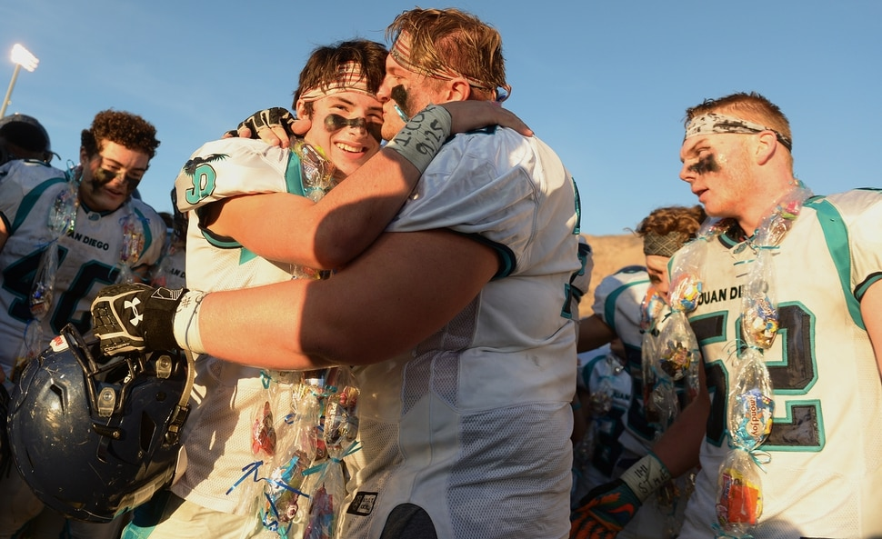 (Leah Hogsten | The Salt Lake Tribune) Juan Diego's Max Butkovich, left, is hugged and kissed by teammate Alex Bemis. Butkovich was reportedly knocked out for a brief moment in the fourth quarter. Juan Diego High School boys' football defeated Morgan High School 45-20 to win the 3A State Championship game Saturday, Nov. 11, 2017 at Weber State University's Stewart Stadium in Ogden.