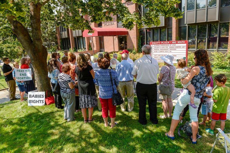 Leah Hogsten | The Salt Lake Tribune Catholic priest, Rev. Jan Bednarz of St. Martin de Porres Parish in Taylorsville, leads the blessed sacrament and exorcism at the Planned Parenthood offices on the Feast of the Assumption. Bednarz was joined by the group, 40 Days for Life Utah, to protest Planned Parenthood.