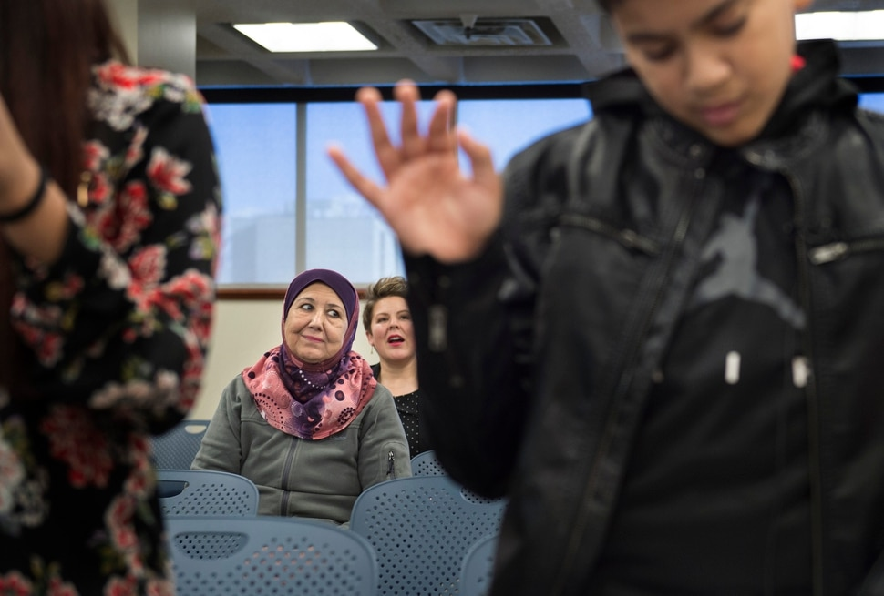 (Scott Sommerdorf | The Salt Lake Tribune) Layla Hussein, the aunt of Haitham Layth Mohammed Ali watches as he, right, takes the pledge and becomes a U.S. citizen during a ceremony in recognition of children who have obtained citizenship through their parents, Thursday, December 28, 2017. Hussein escaped Baghdad in 2002 and her family followed soon after.