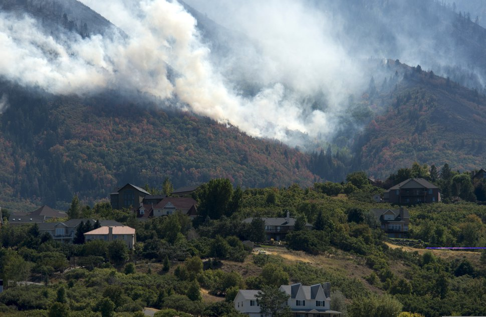 (Rick Egan | Tribune file photo) The Bald Mountain Fire burns in the hills behind the homes in Woodland Hills on Tuesday, Sept. 18, 2018.