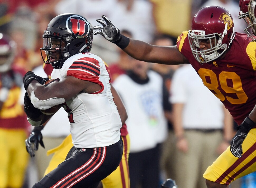 Utah running back Zack Moss, left, runs the ball ahead of Southern California defensive lineman Christian Rector during the first half of an NCAA college football game in Los Angeles, Saturday, Oct. 14, 2017. (AP Photo/Kelvin Kuo)