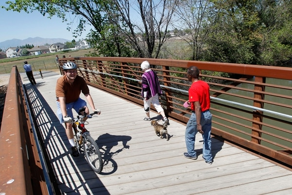 (Al Hartmann | Tribune file photo) Bicyclists and walkers cross the Jordan RIver on a bridge at 1800 N. Redwood Road.
