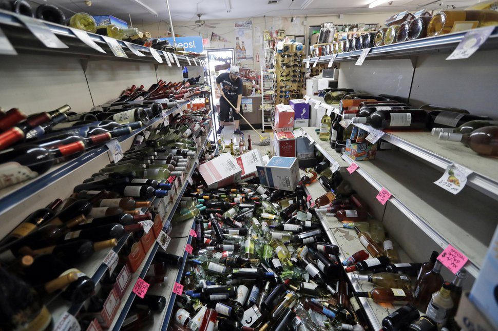 (Marcio Jose Sanchez | The Associated Press) Bottles of wine are strewn in the middle of an aisle as Victor Abdullatif, background center, mops inside of the Eastridge Market, his family's store, Saturday, July 6, 2019, in Ridgecrest, Calif.