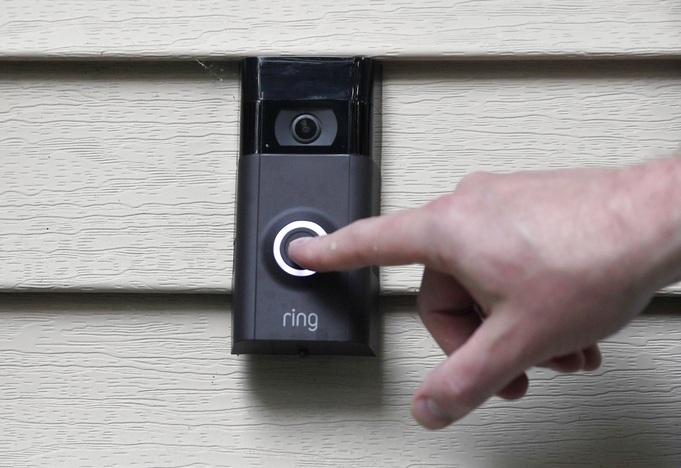 FILE - In this Tuesday, July 16, 2019, file photo, Ernie Field pushes the doorbell on his Ring doorbell camera at his home in Wolcott, Conn. Amazon-owned doorbell camera company Ring is facing questions from a U.S. senator over its partnerships with police departments around the country. Sen. Edward Markey, a Massachusetts Democrat, sent a letter Thursday to Amazon CEO Jeff Bezos raising privacy and civil liberty concerns about Ring cameras that are capturing and storing footage of U.S. neighborhoods.(AP Photo/Jessica Hill, File)