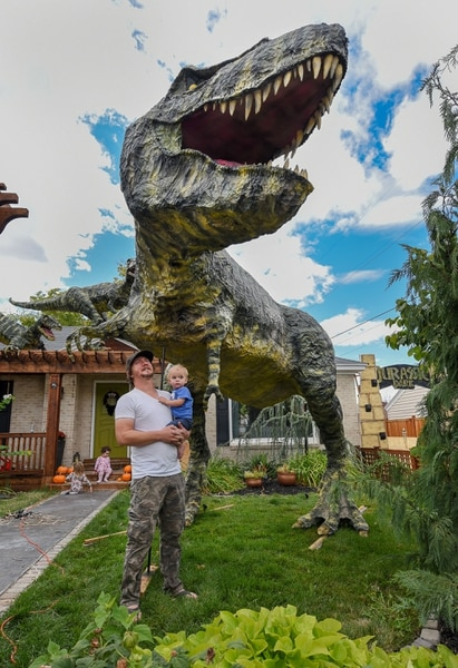 (Francisco Kjolseth | The Salt Lake Tribune) Ammon Smith, holding his nephew Lincoln Smith, 1, has outdone himself once again by going big on his front lawn at 1542 S. 900 East in Salt Lake City for Halloween after constructing a maturing adult-size T. rex along with a pair of velociraptors and pterodactyls. The part-time stay-at-home dad, who made a giant King Kong last year, started construction back in August as he assembled recycled wood, chicken wire, foam, aluminum foil and spray paint for the 12-by-32-foot Jurassic centerpiece and companion pieces.