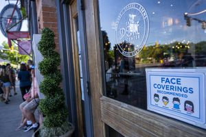 (Rick Egan | The Salt Lake Tribune)  A sign recommending face coverings, on the door of The Spoke On Center, on Street in Moab, on Friday, May 14, 2021.
