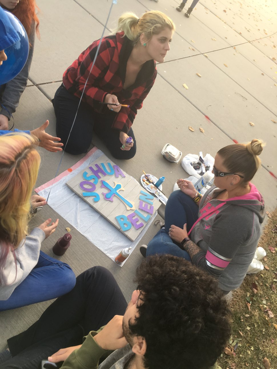 (Mariah Noble | The Salt Lake Tribune) Friends of Joshua Belen gathered to remember him Monday night, after he was shot and killed Saturday, Oct. 21, 2017. Sky Byrne, top left, paints a sign with his name on it. During the gathering, Belen's friends released blue and purple balloons in his memory.