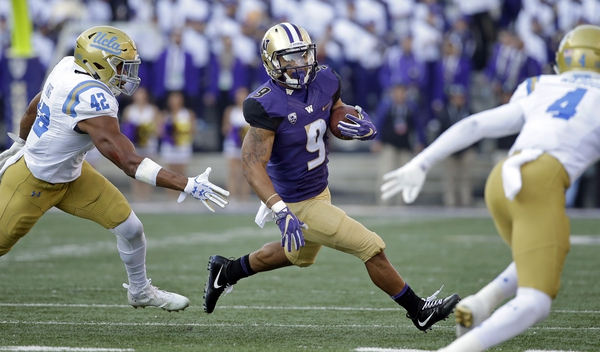 Washington's Myles Gaskin (9) carries the ball between UCLA's Kenny Young and (42) Jaleel Wadood (4) in the first half of an NCAA college football game Saturday, Oct. 28, 2017, in Seattle. (AP Photo/Elaine Thompson)