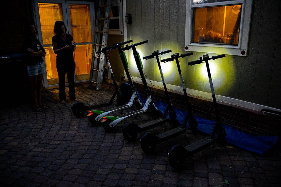 (Trent Nelson | The Salt Lake Tribune) Jenn Hein checks the status of scooters left to charge overnight as she prepares to return them to downtown Salt Lake City locations early Wednesday, Aug. 8, 2018. At left is her daughter Ady Hein.