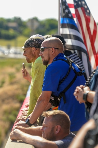 (Leah Hogsten | The Salt Lake Tribune) Brent Jensen, center, and other supporters drape a flag on the SR193 overpass to welcome fallen Ogden City Police Officer Nate Lyday back to Ogden. Lyday was transported from the Medical ExaminerÕs office in West Valley City to a mortuary in Ogden on Friday. Officer Lyday died in a shooting after responding to a domestic violence call May 28, 2020 in Ogden. A suspect was killed and an officer with Adult Probation and Parole was injured at the scene.
