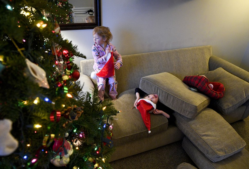 (Isaac Hale photo for The Washington Post) Maggie Riding, 3, left, and her sister Maggie, 5, play with Santa hats in their living room.