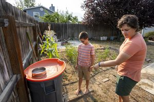 (Rick Egan | The Salt Lake Tribune) Tara Bishop and her 10-year-old son Rock, show where they store rain water to use in a drip system in their garden, at their home in Orem, on Monday, July 12, 2021.