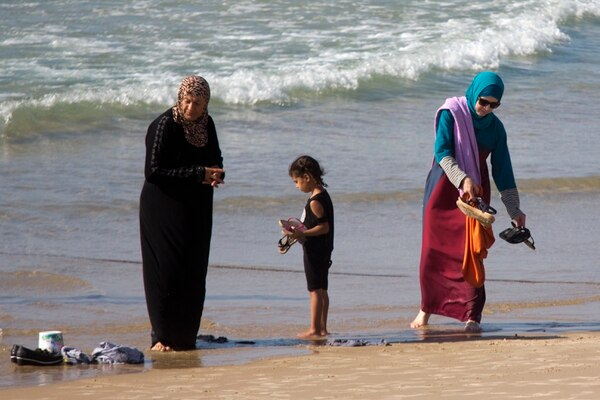 In this Friday, Sept. 2, 2016 photo, Muslim women stand at a beach in Tel Aviv, Israel. France's burkini controversy is boosting the bottom line for Israeli makers of modest swimwear. Israel, home to large populations of conservative Jewish and Muslim women, has cultivated a local industry of modest swimsuits, and the full-body outfits that have caused uproar in France have been a common sight on Israeli beaches for several years. (AP Photo/Ariel Schalit)