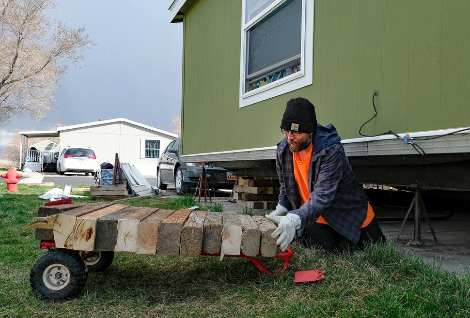 (Francisco Kjolseth | The Salt Lake Tribune) Antonio Tunno risks going under his home in the Western Estates mobile home park in Magna on Monday, March 23, 2020, for the first time since last week's earthquake despite feeling an aftershock earlier in the morning. Using wood blocks, Tunno was trying to shore up his home after multiple jacks under his home had failed, much like many of his surrounding neighbors.