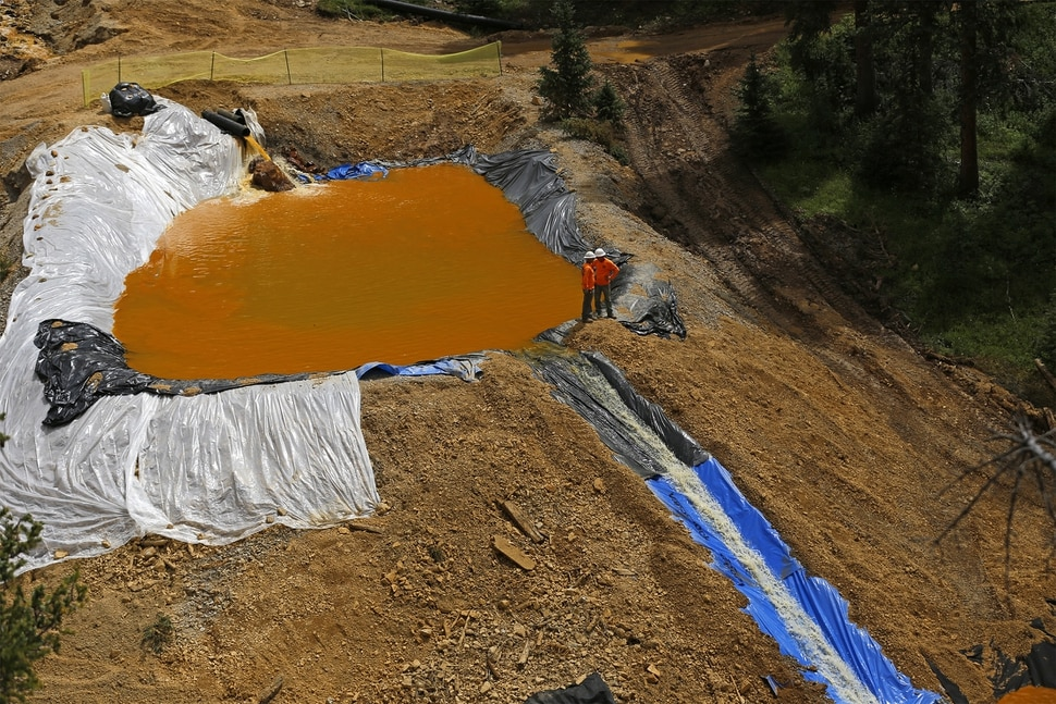 In a Monday, Aug. 10, 2015 photo, environmental restoration employees work at a temporary water treatment holding facility at the Gold King Mine north of Silverton, Colo. Local officials in towns downstream from where millions of gallons of mine waste spilled into the San Juan River are demanding answers about possible long-term threats to the water supply. The 3 million gallons of mine waste included high concentrations of arsenic, lead and other heavy metals. Workers with the EPA accidentally unleashed the spill Wednesday as they inspected the abandoned mine site. (Jon Austria/The Daily Times via AP)