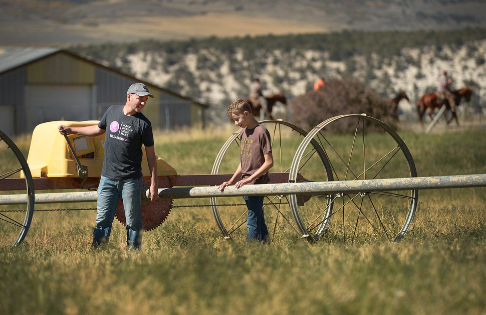 (Leah Hogsten | The Salt Lake Tribune) Spencer Cox and his son Adam, 14, move irrigation pipes in one of the fields on their 14 acre property in preparation of winter.