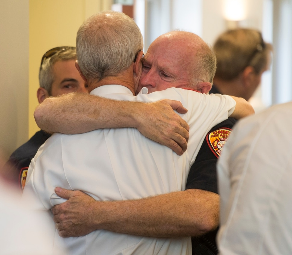 (Rick Egan | The Salt Lake Tribune) Batt. Chief Duane Woolsey with Unified Fire hugs Assistant Chief Mike Watson, before a press conference at Draper City Hall about Matt Burchett, 42, who died fighting wildfires in California. Tuesday, Aug. 14, 2018.
