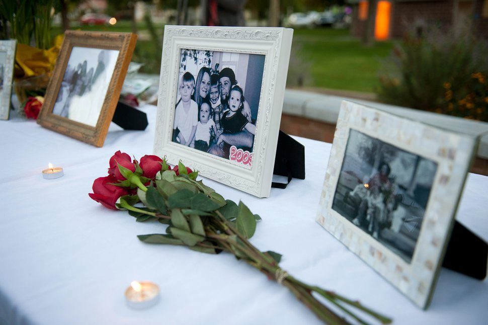 FILE - In this Oct. 2, 2014 file photo, flowers and photos are on display during a vigil for the Strack family at Pioneer Park in Provo, Utah. Police say five members of the Utah family found dead last fall died from methadone and other drugs, and interviews with people who knew them revealed the parents worried about a
