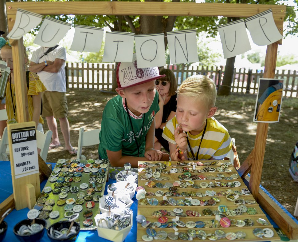 (Leah Hogsten | The Salt Lake Tribune file photo) In 2019, brothers Simon Lewis, 9, left, and Elliot Lewis, 7, right, sold art buttons on Kid Row at the Craft Lake City DIY Festival. Their mother, Lisa Lewis, was behind them.