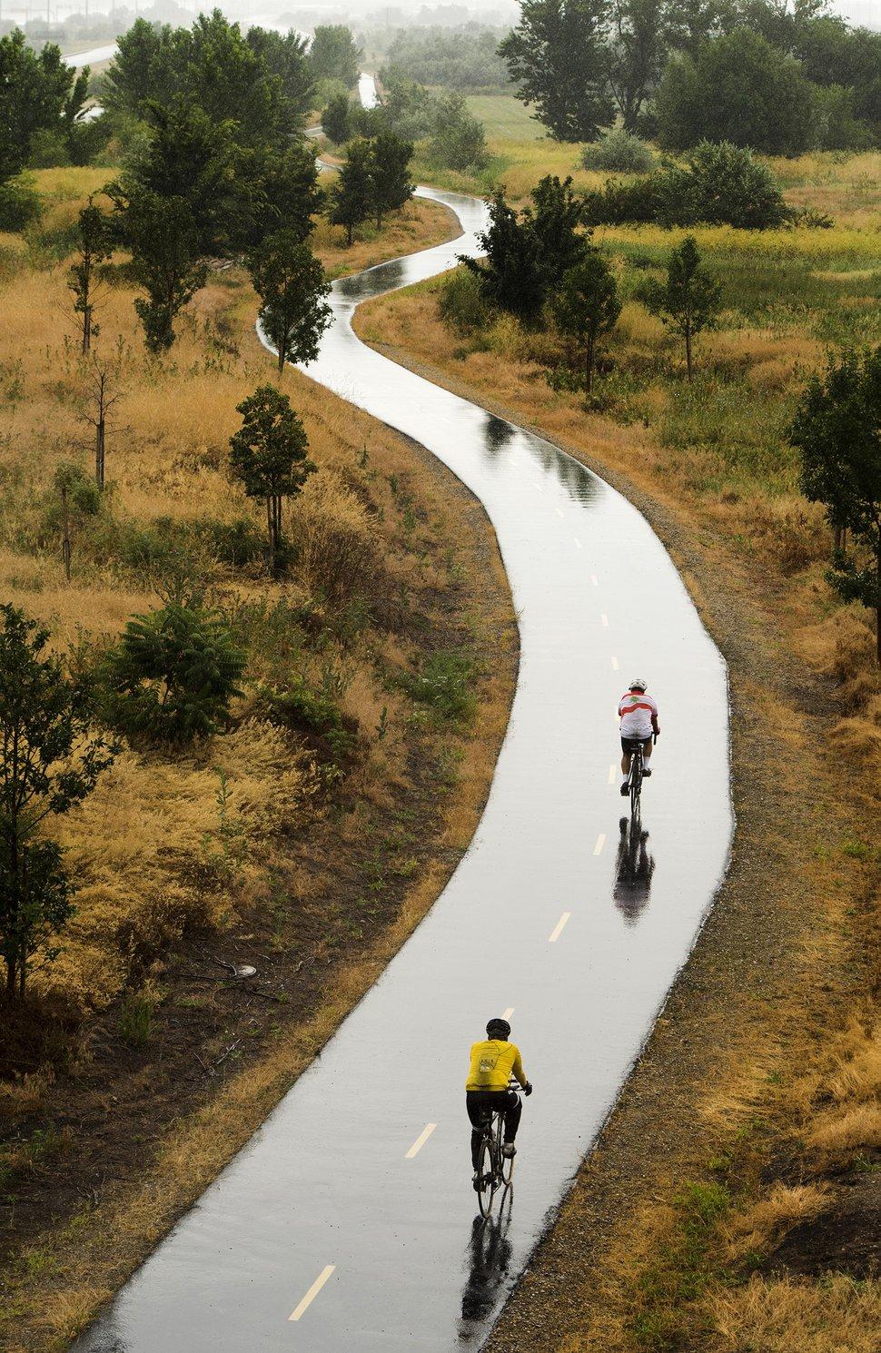 (Rick Egan | Tribune file photo) Cyclists ride the Legacy Parkway Trail in Farmington on a rainy Sunday morning, July 5, 2015.