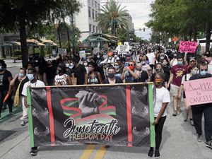 (John Raoux | AP photo)  Demonstrators march through downtown Orlando, Fla., during a Juneteenth event Friday, June 19, 2020. Juneteenth marks the day in 1865 when federal troops arrived in Galveston, Texas, to take control of the state and ensure all enslaved people be freed, more than two years after the Emancipation Proclamation.