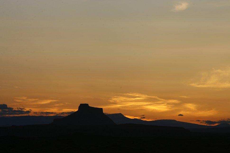 (Rick Egan | Tribune file photo) The sun sets behind Factory Butte, near Hanksville, Utah, May 19, 2010.