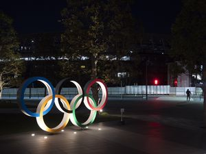 """(Jae C. Hong   AP) The Olympic rings stand near the New National Stadium in Tokyo, Tuesday, March 24, 2020. IOC President Thomas Bach has agreed """"100%"""" to a proposal of postponing the Tokyo Olympics for about one year until 2021 because of the coronavirus outbreak, Japanese Prime Minister Shinzo Abe said Tuesday."""