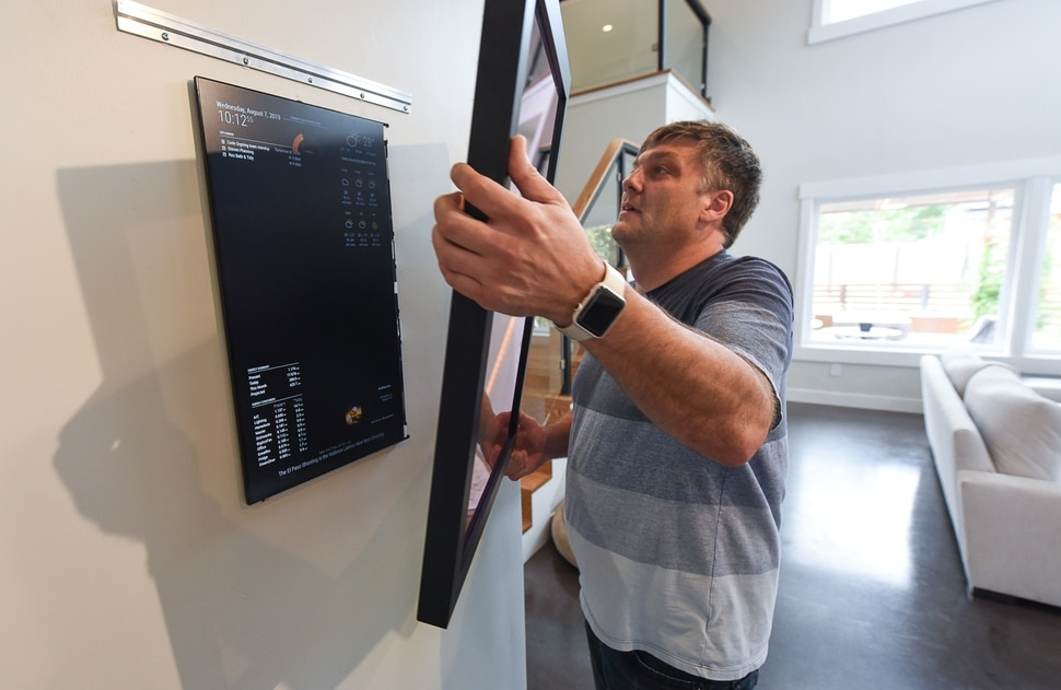 (Francisco Kjolseth | The Salt Lake Tribune) Peter Bartok, a resident at Living Zenith, a community of five energy-efficient homes near Liberty Park, shows off the magic mirror that discretely hides the screen that displays the energy use and vitals of his house in real-time.