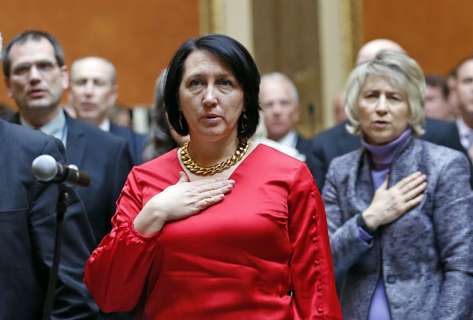 Republican Rep. Karianne Lisonbee of Clearfield stands for the national anthem to open the 2018 Utah Legislature Monday, Jan. 22, 2018, in Salt Lake City. Lisonbee wants to bar doctors from performing abortions sought because of a diagnosis of Down syndrome even though legislative lawyers warn that there's a high probability that a court will find the law unconstitutional. (AP Photo/Rick Bowmer)