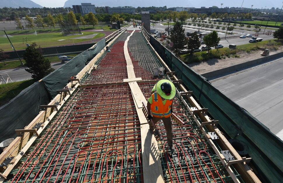 (Francisco Kjolseth | The Salt Lake Tribune) UDOT gives a tour of the state's new longest pedestrian bridge on Thursday, August 20, 2020, connecting Utah Valley University in Orem to student housing and the community on the West side of I-15. Crews are finishing up an extensive hydronic heating system that will pump warm water to keep the bridge clear of snow in the winters, as it gets ready to pour concrete for the walking surface. UDOT will close I-15 in both directions this weekend for work on the nearly 1,000 foot bridge that is 15 feet wide to accommodate pedestrians, cyclists and scooters. Elevators and stairs with small ramps to push up bicycles will be on each side of the bridge.