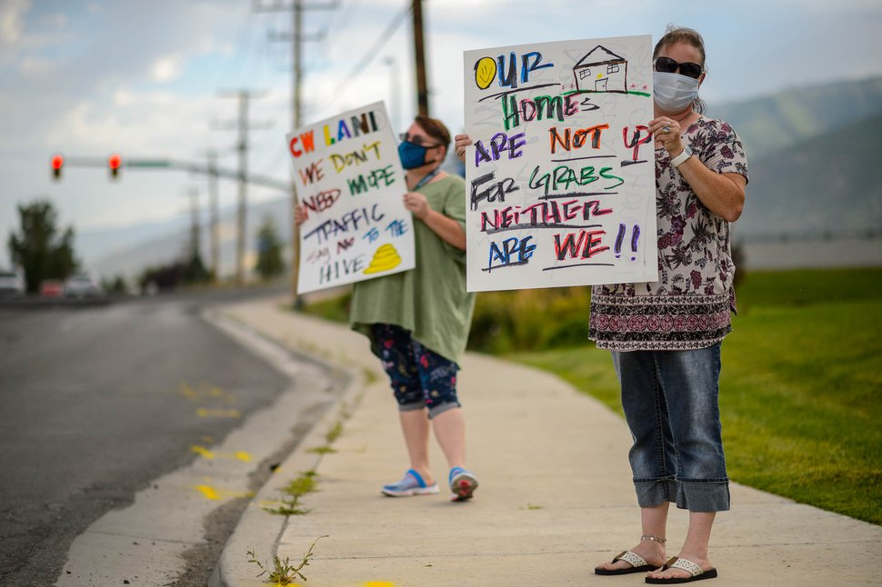 (Trent Nelson | The Salt Lake Tribune) Shaunna Summers and Brandi Dudley protest possible evictions in front of the offices of C.W. Land in Centerville on Monday, July 13, 2020.