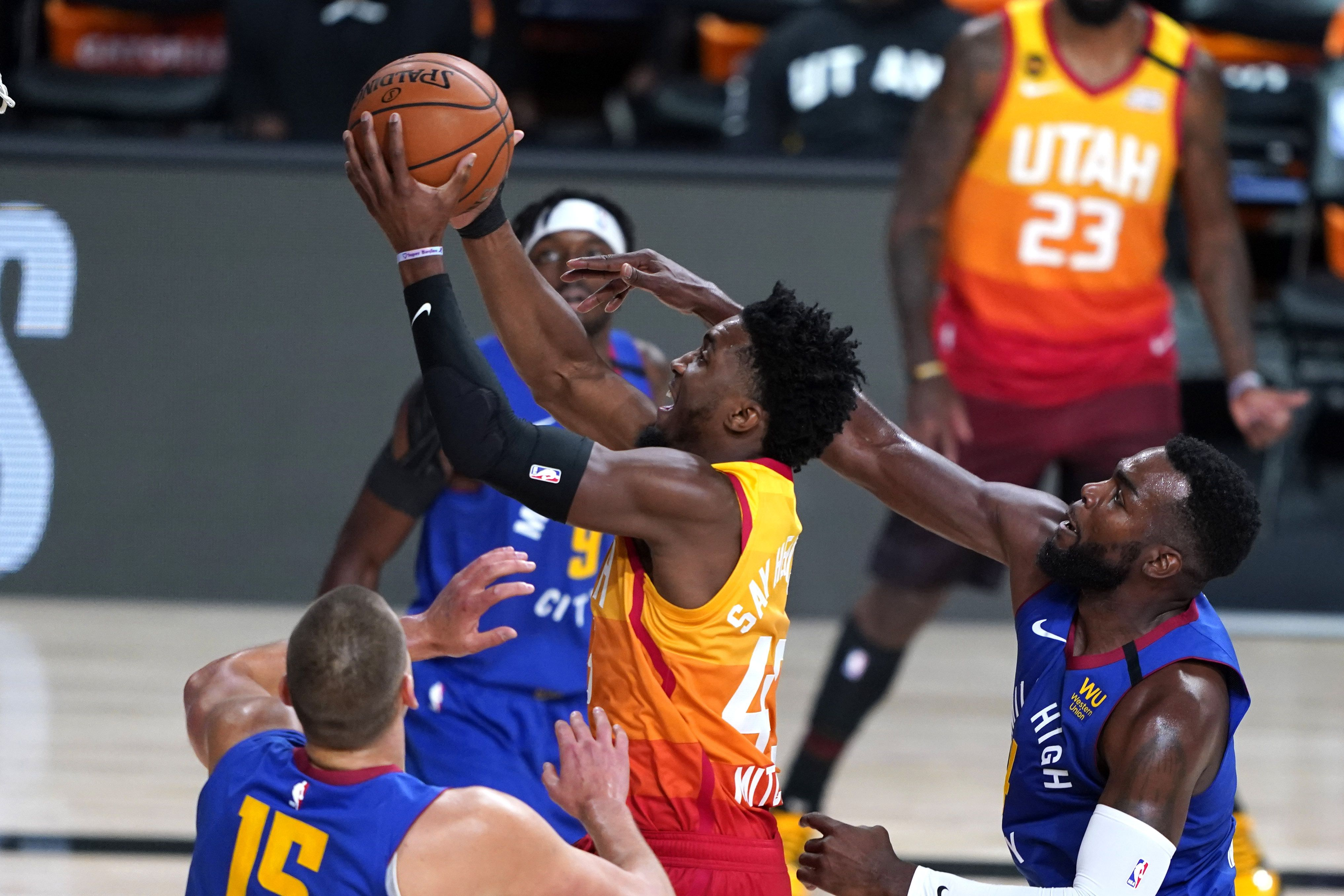 Utah Jazz's Donovan Mitchell (45) goes up for a shot as Denver Nuggets' Paul Millsap (4), right, defends during the first half of an NBA basketball first round playoff game Sunday, Aug. 23, 2020, in Lake Buena Vista, Fla. (AP Photo/Ashley Landis, Pool)