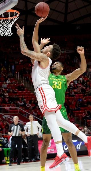 (Leah Hogsten | The Salt Lake Tribune) Utah Utes forward Timmy Allen (1) drives to the net around Oregon Ducks forward Francis Okoro (33) as the University of Utah basketball team hosts No. 4 Oregon, Jan. 4, 2020, at the Huntsman Center.