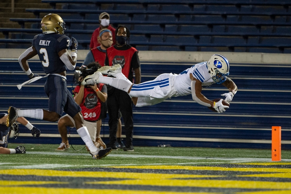 BYU running back Tyler Allgeier, right, dives for a touchdown as Navy cornerback Cameron Kinley (3) looks on during the first half of an NCAA college football game, Monday, Sept. 7, 2020, in Annapolis, Md. (AP Photo/Tommy Gilligan)