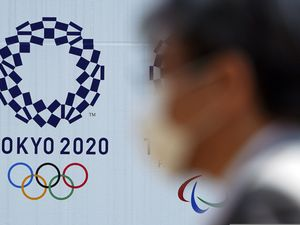 """(Eugene Hoshiko   AP) In this April 2, 2020 photo, a man wearing a face mask walks near the logo of the Tokyo 2020 Olympics, in Tokyo. Tokyo organizers said Tuesday, April 14, 2020 they have no """"B Plan"""" for again rescheduling the Olympics, which were postponed until next year by the virus pandemic. They say they are going forward under the assumption the Olympics will open on July 23, 2021."""