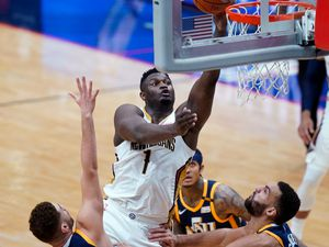 New Orleans Pelicans forward Zion Williamson (1) goes to the basket over Utah Jazz forward Georges Niang, left, and center Rudy Gobert, right, in the first half of an NBA basketball game in New Orleans, Monday, March 1, 2021. (AP Photo/Gerald Herbert)