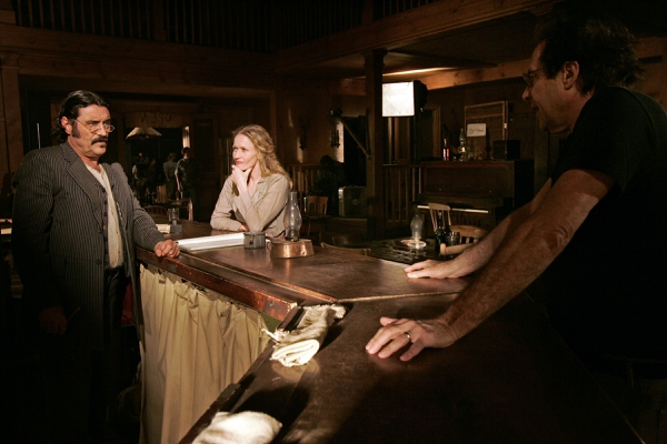 (Kevork Djansezian | Associated Press) This 2005 file photo shows actors Ian McShane, who portrays Al Swearengen, left, and Paula Malcomson, who portrays Trixie, center, on the set with David Milch, creator of the HBO series