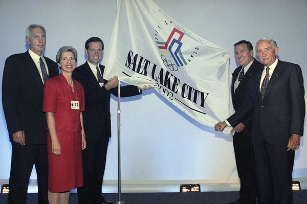 Members of the Salt Lake City delegation for the 2002 Winter Olympics, from left to right, Harvey Shiller, U.S. Olympic Committee executive director, Salt Lake City mayor Deedee Corradini, Utah governor Mike Leavitt, Tom Welch, President of the Olympic Bid committee and G. Franck Joklik, chairman of the Olympic Bid committee pose with their flag in Paris on Saturday, August 27, 1994 after they made their presentation to the executive board of the International Olympic Committed. (AP Photo/Francois Mori)