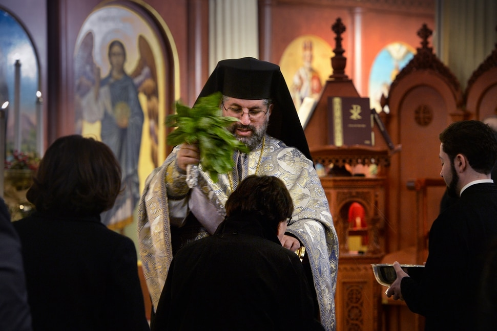 (Scott Sommerdorf | The Salt Lake Tribune) The Very Rev. Archimandrite George Nikas blesses congregants with holy water from a bouquet of basil as he conducts the Epiphany service (also called Theophany in Orthodox), as holy water is blessed, at Holy Trinity Cathedral, Saturday, January 6, 2018.