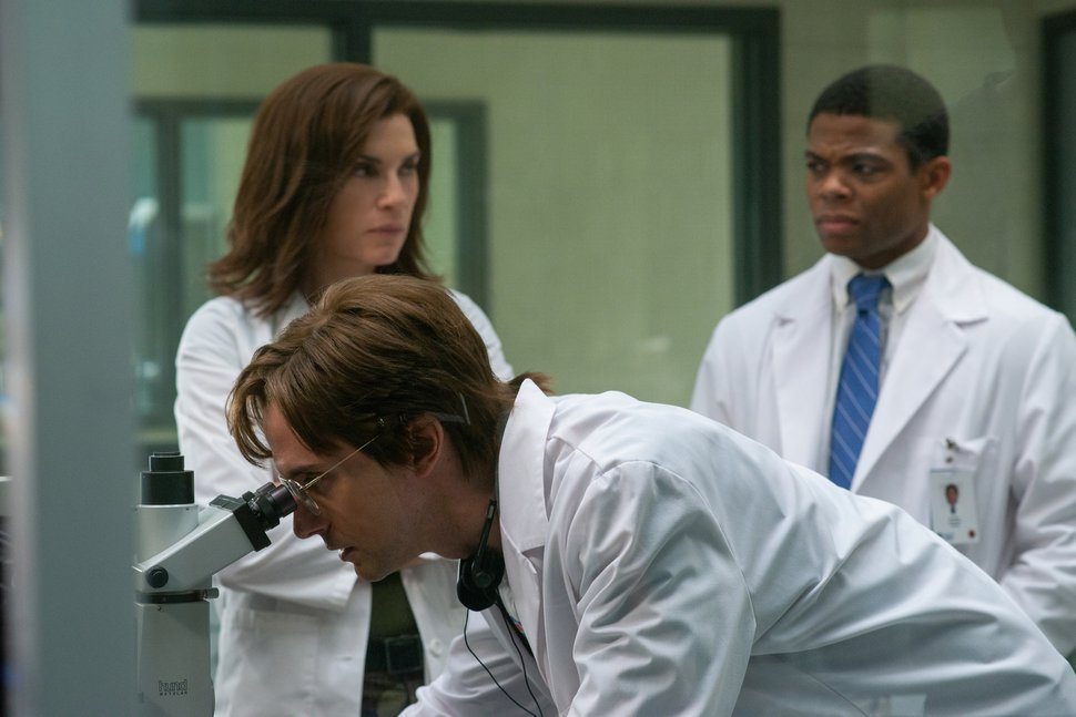 (National Geographic | Amanda Matlovich) Dr. Peter Jahrling (Topher Grace), a civilian virologist, looks through the microscope eyepiece as Dr. Nancy Jaax (Julianna Margulies) and Ben Gellis (Paul James) look on.