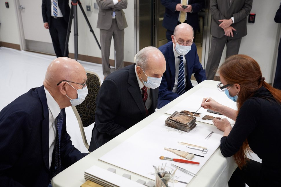 (Photo courtesy of The Church of Jesus Christ of Latter-day Saints) Emiline Twitchell, a conservator at the Church History Library, shows contents from the capstone of the Salt Lake Temple to the First Presidency on May 20, 2020.